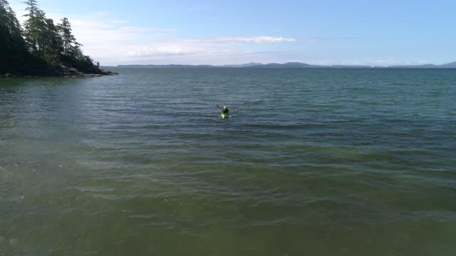 Drone Flying Slow Motion Over Man Paddling Kayak in Ocean video
