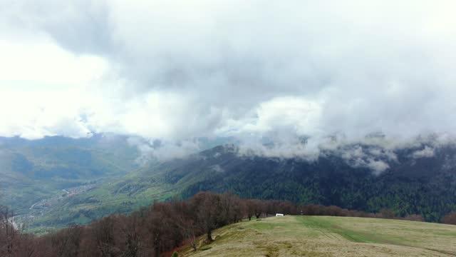 vídeos de stock, filmes e b-roll de drone voando através da neblina matinal nas montanhas da primavera. vista aérea de névoa, nuvens e neblina pairando sobre uma floresta de madeira após uma chuva - ucrânia