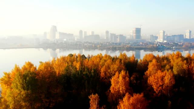 drohne fliegt in richtung schöne sonnenaufgang stadt gebäude panorama über erstaunliche seewasser und sonnige gelbe herbstbäume. - weißrussland stock-videos und b-roll-filmmaterial