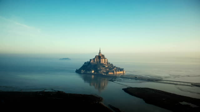 Drone flying towards epic sunrise Mont Saint Michel, famous island fortress castle surrounded by foggy sea in Normandy. Drone flying towards epic sunrise Mont Saint Michel, famous island fortress castle surrounded by foggy sea in Normandy. Incredible ethereal fantasy scenery, ancient atmospheric travel destination. normandy stock videos & royalty-free footage