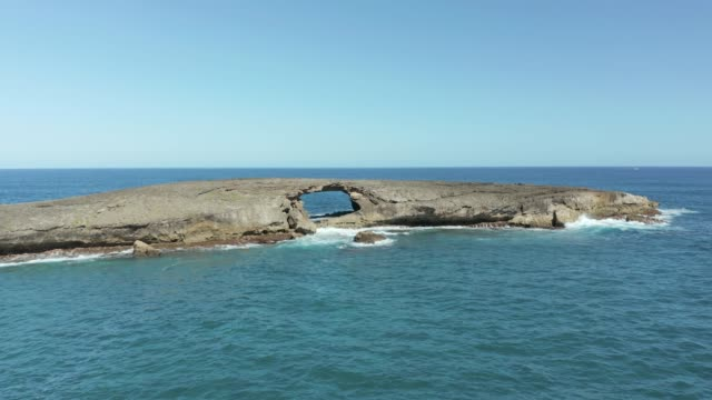 Drone flying towards small island with sea arch at Laie Point on Oahu in Hawaii - video