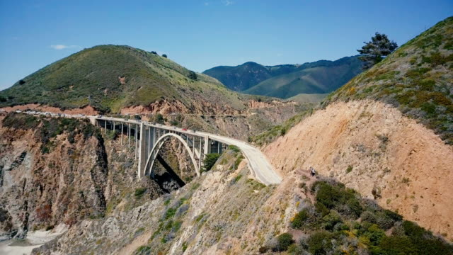 drone flying up from man and woman sitting together to reveal epic beautiful view of bixby creek bridge in big sur usa. - telecomando background video stock e b–roll