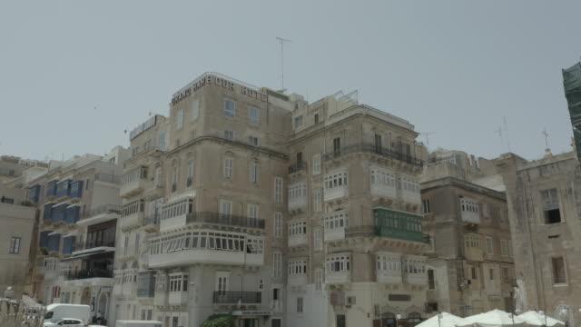 Drone flying up through beautiful old street,Valletta,Malta . Old, vintage windows, balconies. - 4K