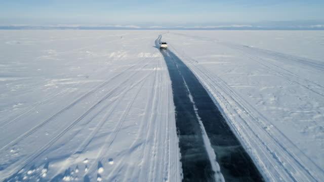 氷の上に白い suv 車に続くドローン。雪で覆われたバイカル湖表面の美しい冬の風景 - シベリア点の映像素材/bロール
