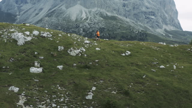 Drone following a young man running on the Dolomites, European Alps of Italy
