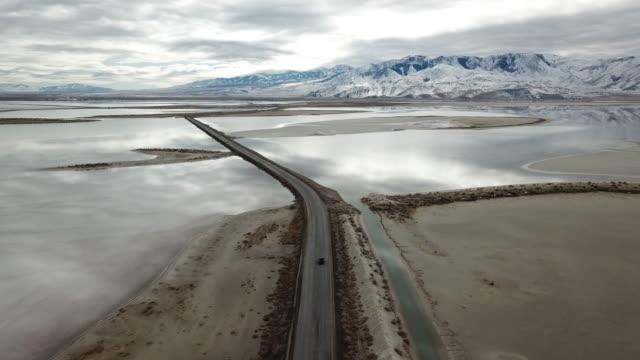vidéos et rushes de drone suivant la conduite automobile - lac salé