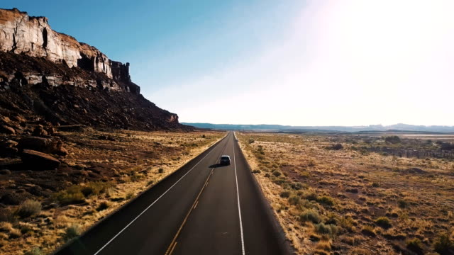 Drone follows car driving along highway road between epic steep canyon mountain ridge and amazing desert skyline in USA. Drone follows car driving along highway road between epic steep canyon mountain ridge and amazing desert skyline in USA. Beautiful cinematic opening shot of amazing American nature landscape. eternity stock videos & royalty-free footage