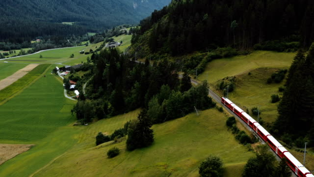 Drone follows famous red Glacier Express train moving along epic summer Switzerland Alps, adventure tourism concept.