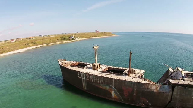 Drone footage along  the shipwreck Evangelia , showing advanced structural damage of the upper deck and the ship broken in two  , stranded on the Black Sea coast , Romania , aerial view video