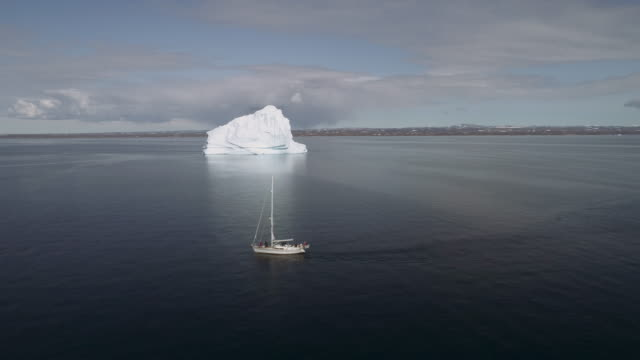 vídeos de stock e filmes b-roll de drone footage flying past a sailing boat large iceberg in the arctic, greenland, scoresby sund, aerial footage of yacht and iceberg - iceberg