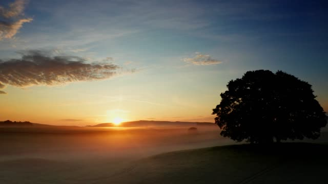 Drone Footage of a Misty Sunrise, Yorkshire Dales,UK Sunrise over farmland near the Yorkshire Dales village of Eshton a small village and civil parish in the Craven district of North Yorkshire, England. At the 2011 Census the population was less than 100 and is included in the civil parish of Flasby with Winterburn. In 2015, North Yorkshire County Council estimated the population to be 70 dawn stock videos & royalty-free footage