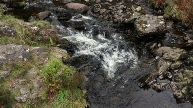 Drone footage of a small river flowing over rocks in rural Scotland video