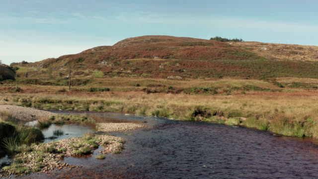 Drone footage of a small river in rural Scotland A river tinted brown by peat in a remote rural part of Dumfries and Galloway in south west Scotland galloway scotland stock videos & royalty-free footage