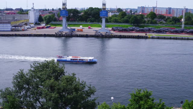 Drone footage of a water tram passing by the Westerplatte Monument. Shot is taken in peninsula in Gdańsk harbor channel and Dead Vistula area, during a sunny summer day in Poland. gdansk stock videos & royalty-free footage