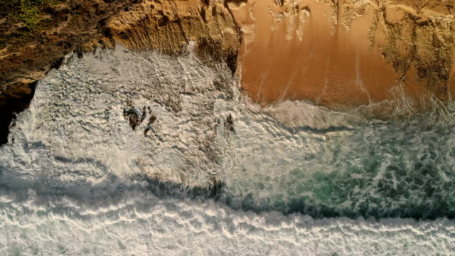 dalgalar breaking kayalık sahil şeridi üzerinde 4k dron görüntüleri. - okyanus gemisi stok videoları ve detay görüntü çekimi