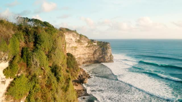 vídeos de stock e filmes b-roll de 4k drone footage of clif in south bali sunset spot - transatlântico