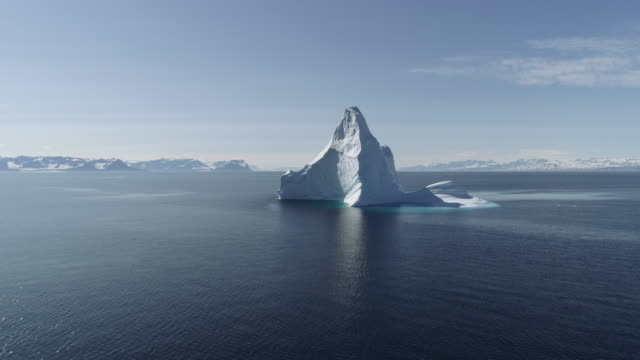 Drone Footage of Giant Iceberg! Aerial Drone Footage Flying Towards A Beautiful Large Cathedral Shaped Iceberg in Scoresby Sund in Greenland Drone footage shot in the Arctic in Scoresby Sund, Greenland on a remote polar expedition. A drone shot captures an aerial view of a large iceberg in a fjord in Greenland in a remote area. The shot passes towards the iceberg with mountains in the background. The shot is great for communicating vacations, sailing, tourism, adventure travel, exploration and climate change and global warming which is affecting the ice in this area. Perfect footage for your travel video. icecap stock videos & royalty-free footage