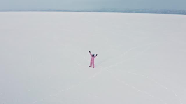 drönarbilder på enstaka asiatisk kvinna som viftade med händerna i nöd på avlägsen plats frusen sjötornräsk en molnig dag i abisko sverige norra halvklotet - norrbotten bildbanksvideor och videomaterial från bakom kulisserna