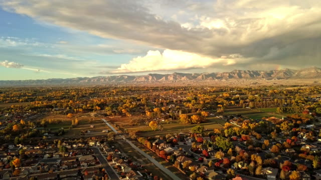 drone footage of stormy evening sunset with moody clouds over grand junction colorado - колорадо стоковые видео и кадры b-roll