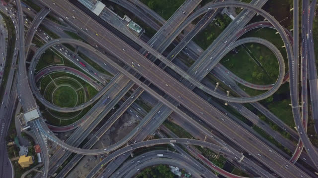 drone footage of top view of highway road junctions. the intersecting freeway road overpass the eastern outer ring road of bangkok, thailand.zoom out shot - ingrandimento video stock e b–roll