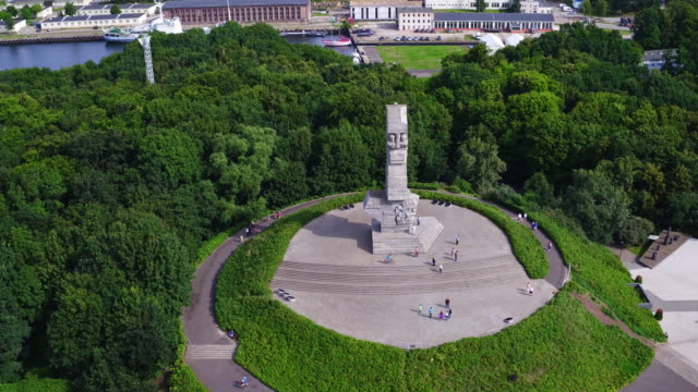 Drone footage of Westerplatte Monument on a peninsula in Gdańsk harbor channel. Shot is taken during a sunny day in Poland. gdansk stock videos & royalty-free footage