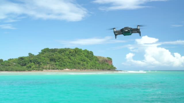 A drone hovers in place then flies towards a tropical island. Isolated drone.
