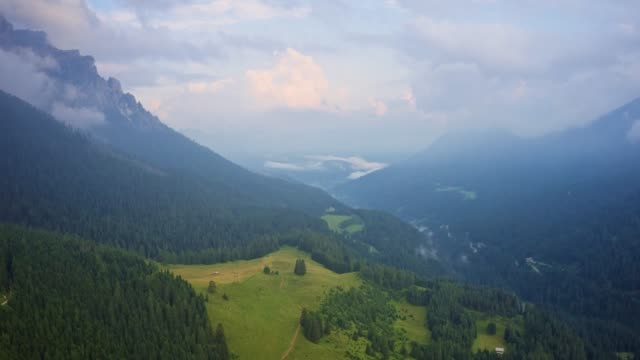 Drone hyper lapse of a mountain peaks in summer with meadow fields and trees