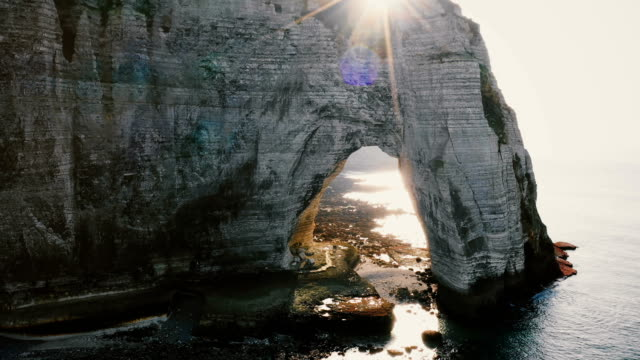 Drone is flying away from young happy tourist newlywed couple in epic natural rocky arch at famous white Normandy cliffs Drone is flying away from young happy tourist newlywed couple in epic natural rocky arch at famous white Normandy cliffs. Man and woman taking beautiful drone selfie under amazing sunset rocky shore. normandy stock videos & royalty-free footage