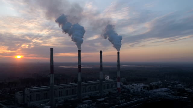 Drone is flying high above thermal power plant and smoke cloud is coming from chimney
