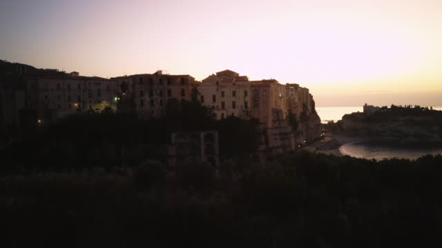 drone is landing overlooking the medieval houses on the rock. - video di tropea video stock e b–roll