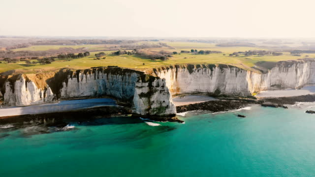 Drone is slowly approaching epic sunset white chalk cliffs and green fields above azure sea coastline in Normandy.