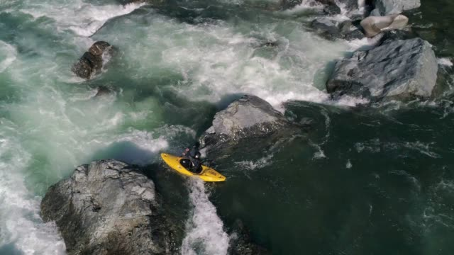 Drone Kayaking Whitewater Rapids Slow Motion Epic slowmo aerial following extreme sports athlete paddling kayak over small waterfall in vibrant turquoise raging river waters rapids river stock videos & royalty-free footage