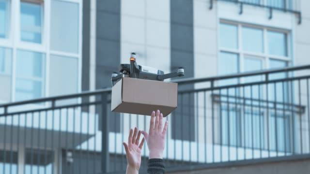 Drone landing with shipping box into female recipient hands Drone landing with shipping box into female recipient hands in city area landing touching down stock videos & royalty-free footage