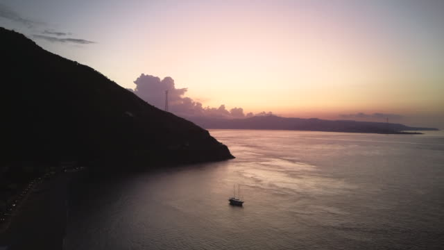 drone makes an evening flight over the coast, there is a yacht in the sea. - video di tropea video stock e b–roll
