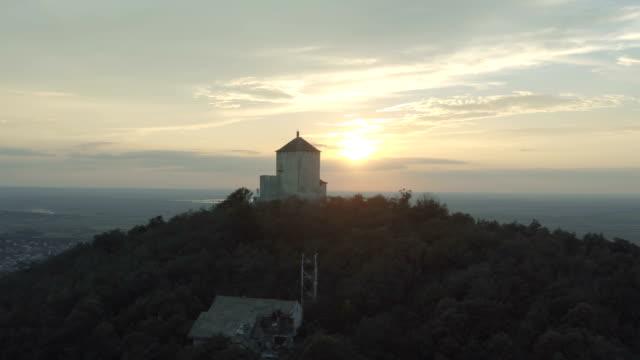 bir taş ortaçağ kulesi arkasında gün batımı drone hareketli çekim - sale stok videoları ve detay görüntü çekimi