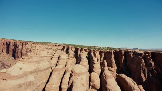 drohne über canyon bei moab, utah: badlands und felsige gipfel - hochplateau stock-videos und b-roll-filmmaterial
