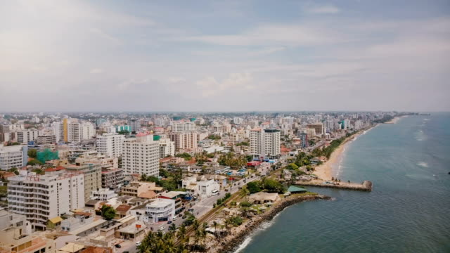 Drone panning left over amazing coastline and buildings of Colombo, Sri Lanka. Amazing aerial shot of Asian architecture Drone panning left over amazing coastline and buildings of Colombo, Sri Lanka. Amazing aerial shot of modern Asian small town architecture, street daily traffic and ocean shoreline on a sunny day. colombo stock videos & royalty-free footage