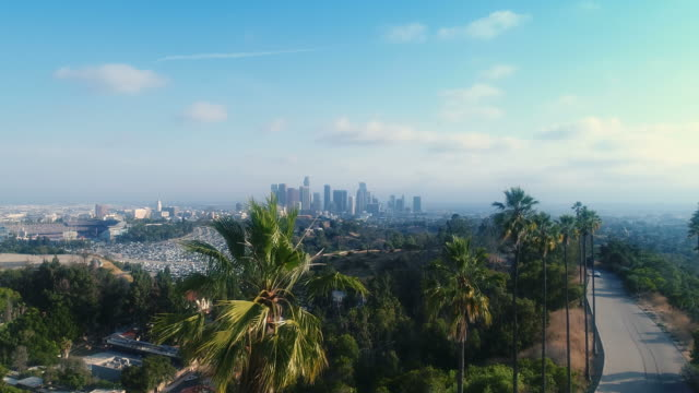 Drone pedestal up to amazing downtown Los Angeles skyline above Dodger Stadium - UHD 4k resolution video