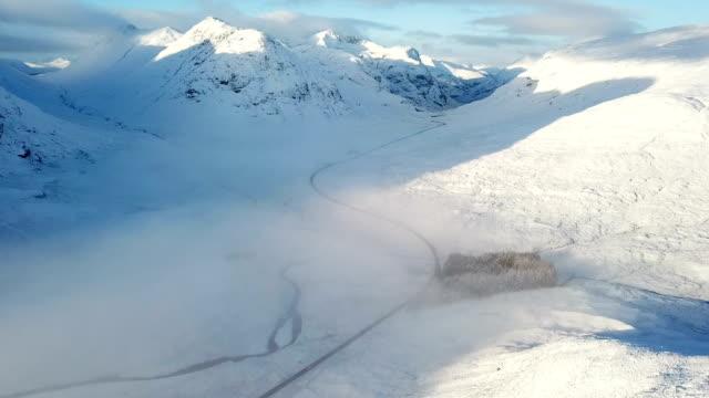 stockvideo's en b-roll-footage met drone perspectief vliegen over ruige besneeuwde hoogland bergen - sneeuwkap