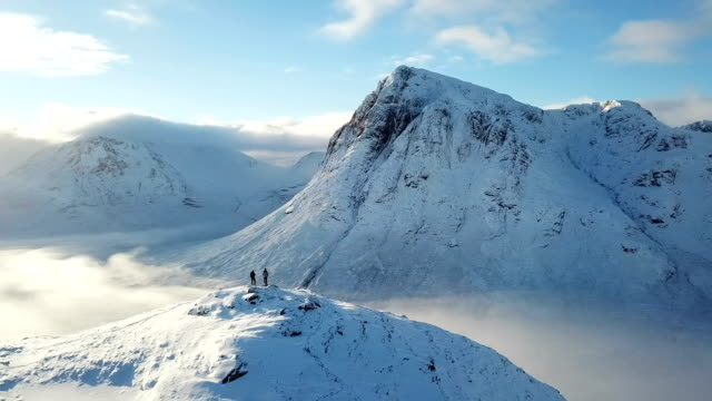 Drone perspective flying over rugged snowy highland mountains