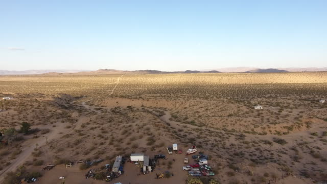 Drone point of view at Mojave desert Drone point of view at Mojave desert with abandoned houses, parking lot on summer time mojave desert stock videos & royalty-free footage