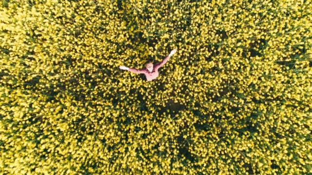 日当たりの良い農村黄色い菜の花畑、リアルタイムで帽子を投げてドローンの視点熱狂的な農家 - スロベニア点の映像素材/bロール