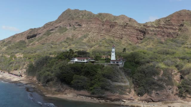 Drone point of view moving towards the Diamond Head lighthouse from the ocean in Hawaii - video