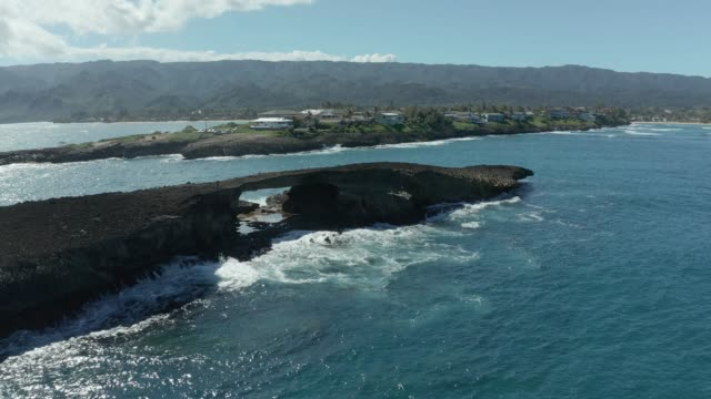 Drone point of view of small island with sea arch at Laie Point on Oahu in Hawaii - video