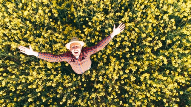 Drone point of view portrait exuberant farmer in sunny,rural yellow canola field,real time