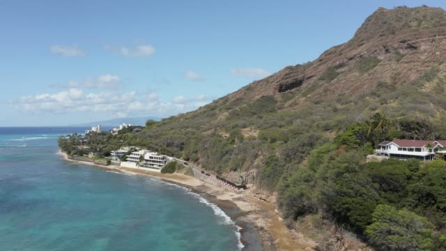 Drone point of view rotating around the coastline by the Diamond Head lighthouse from the ocean in Hawaii - video