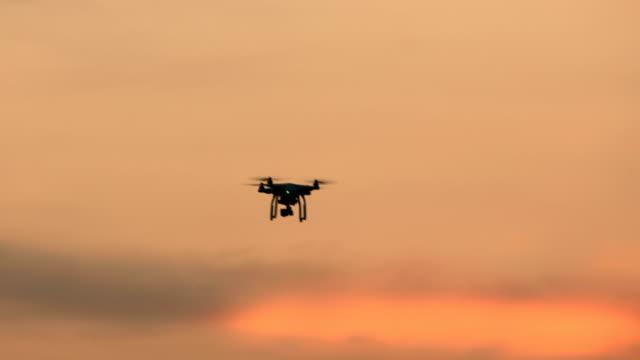 vídeos de stock, filmes e b-roll de drone quad helicóptero com câmera digital de voo pairando sobre o sol - multicóptero