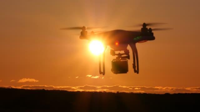 일몰 시 카메라와 함께 비행 하는 무인 항공기 quadcopter multirotor - 무인항공기 스톡 비디오 및 b-롤 화면