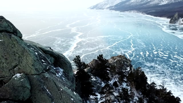 vídeos de stock e filmes b-roll de drone rises above the frozen crystal ice of the lake baikal. top view. natural background and patterns - lago baikal