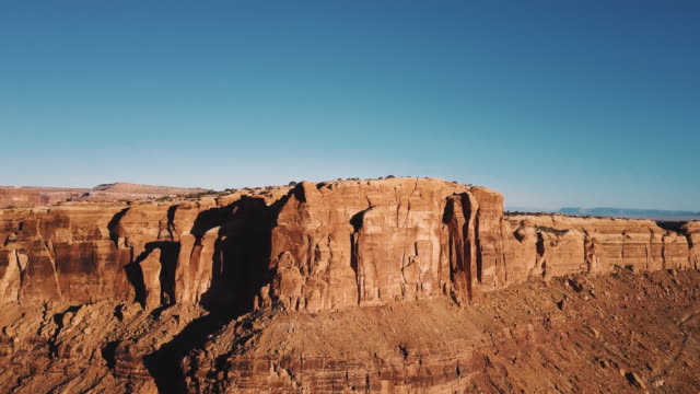 drohne erhebt sich über bergrücken, epische sonnigen wüste wildnis mit atemberaubenden felswand canyon skyline zu offenbaren. - sandstein stock-videos und b-roll-filmmaterial